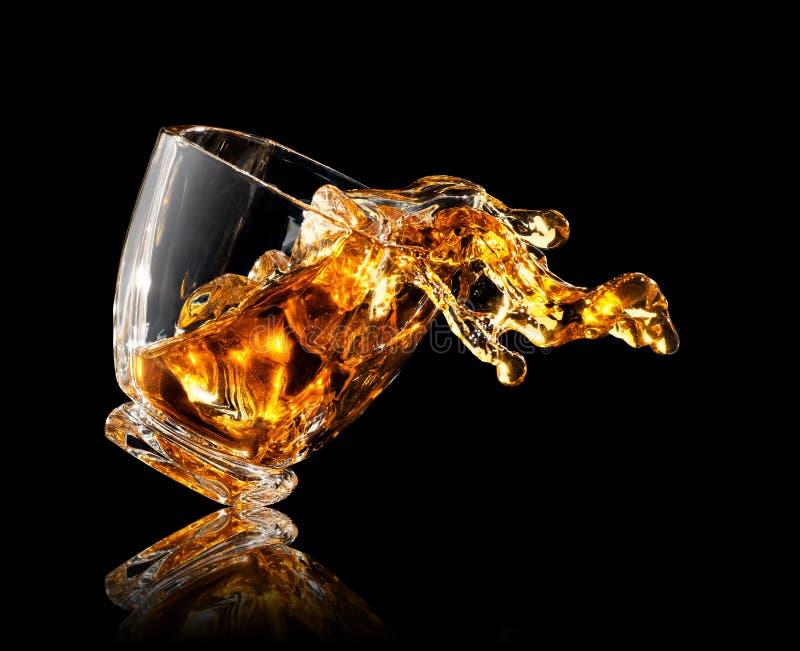 Plons van whisky in glas stock foto's