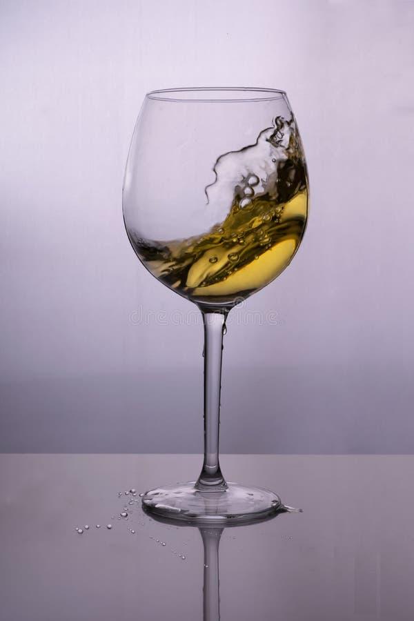 Plons van witte wijn in een glas royalty-vrije stock afbeeldingen
