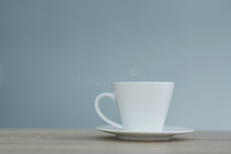 Plons in witte kop van koffie op houten lijst royalty-vrije stock fotografie
