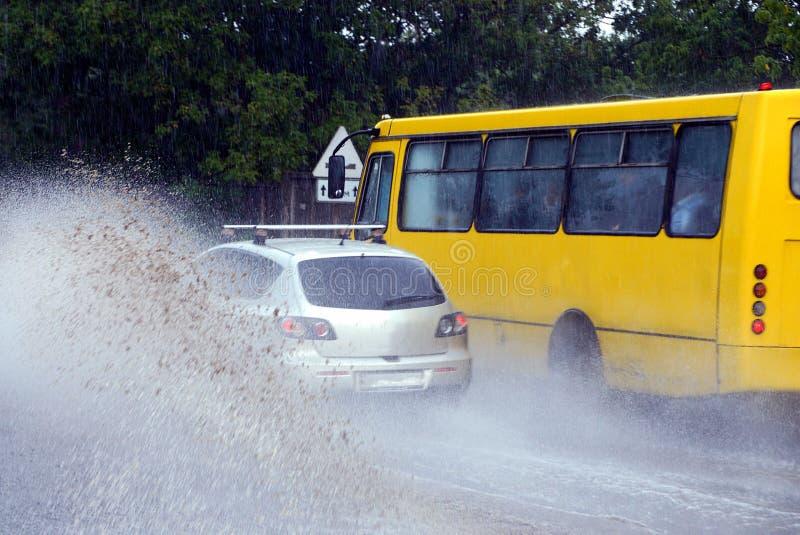 Plonsen van de wielen van een auto en een gele bus stock foto's