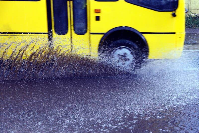 Plonsen van onder de wielen van de bus tijdens zware regen stock foto