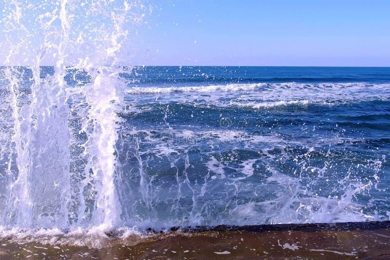 Plonsen van water van de stormachtige golven die op de golfbreker op waterkant breken Blauwe Duidelijke Hemel stock afbeeldingen
