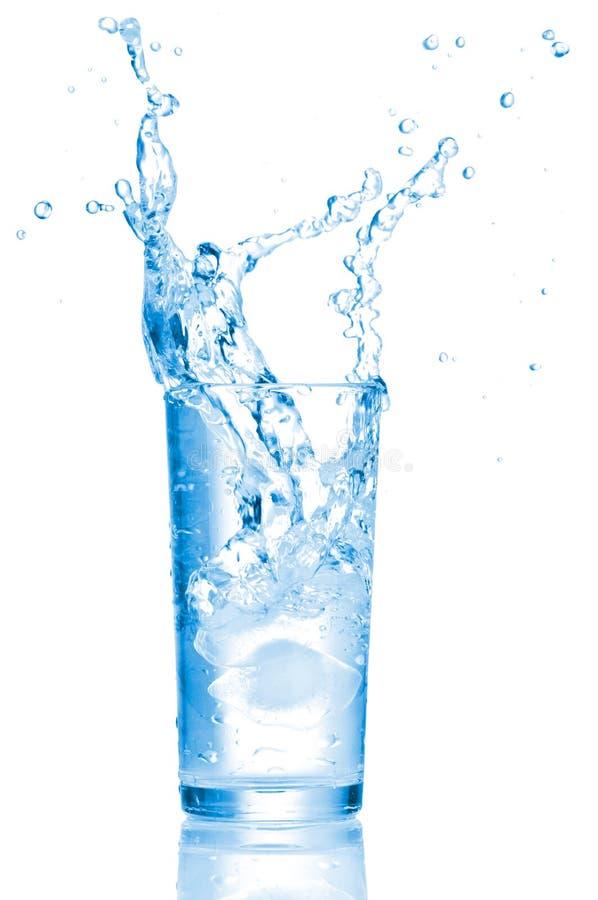 Plonsen van water in een glas royalty-vrije stock afbeeldingen