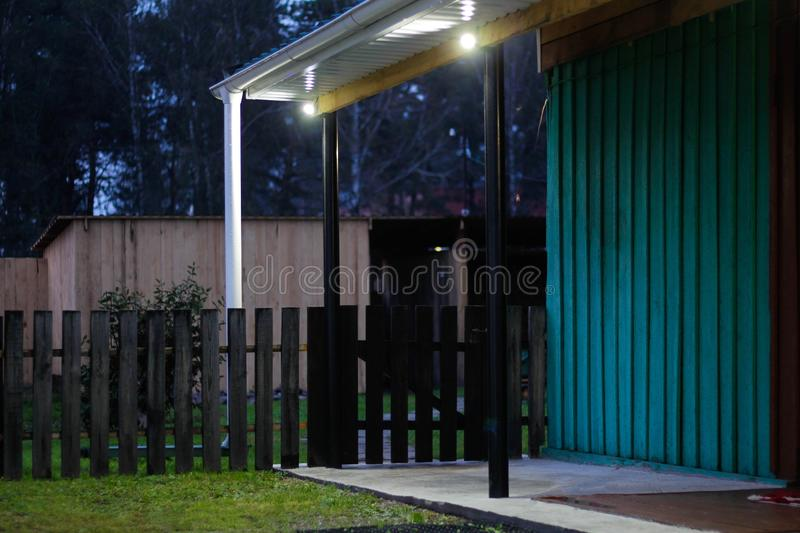 Plot of a private house. Wooden fence, roof on metal poles, gutters, lighting royalty free stock image
