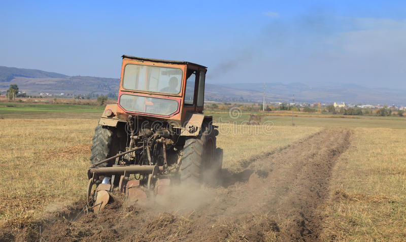 Ploughing. Image of a field with a tractor ploughing stock photography