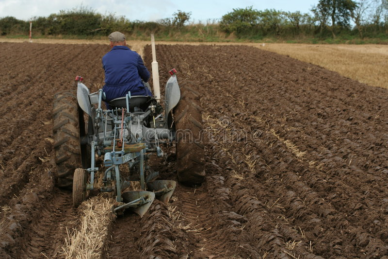 Ploughing. Farmer ploughing field on an old fashioned tractor stock photos