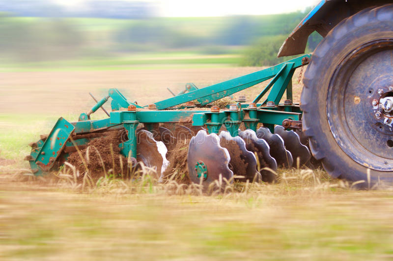 Ploughing the field. Tractor ploughing the field. Motion blur was done for effect to emphasize speed stock images