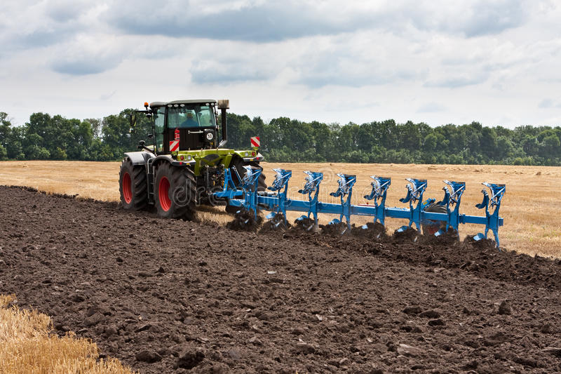 Ploughing of land. With tractor in summer stock image