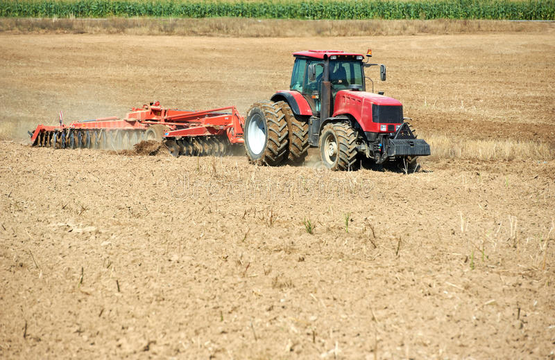 Ploughing tractor at field cultivation work royalty free stock images