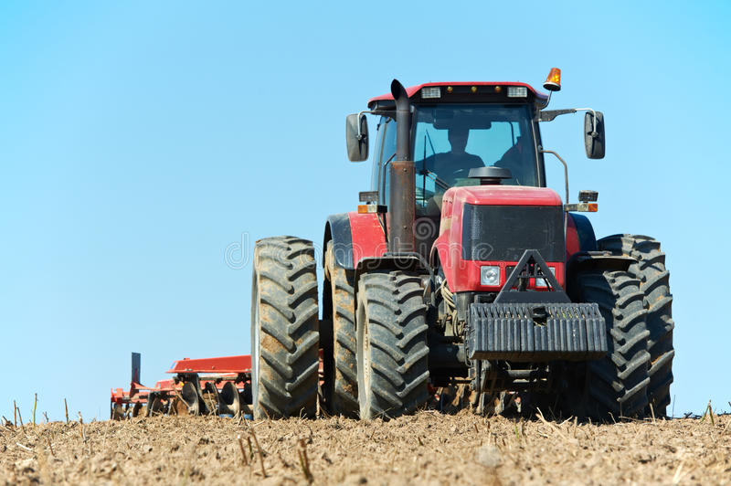 Ploughing tractor at field cultivation work stock photography