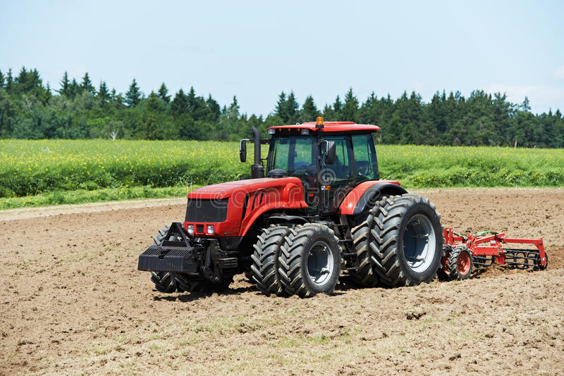Ploughing tractor at field cultivation work stock photo