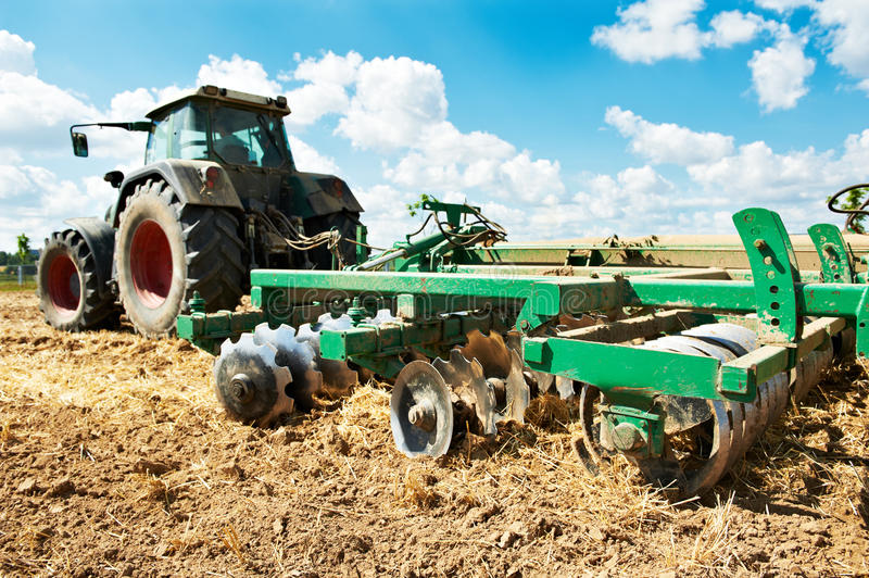 Ploughing tractor at field cultivation work stock image