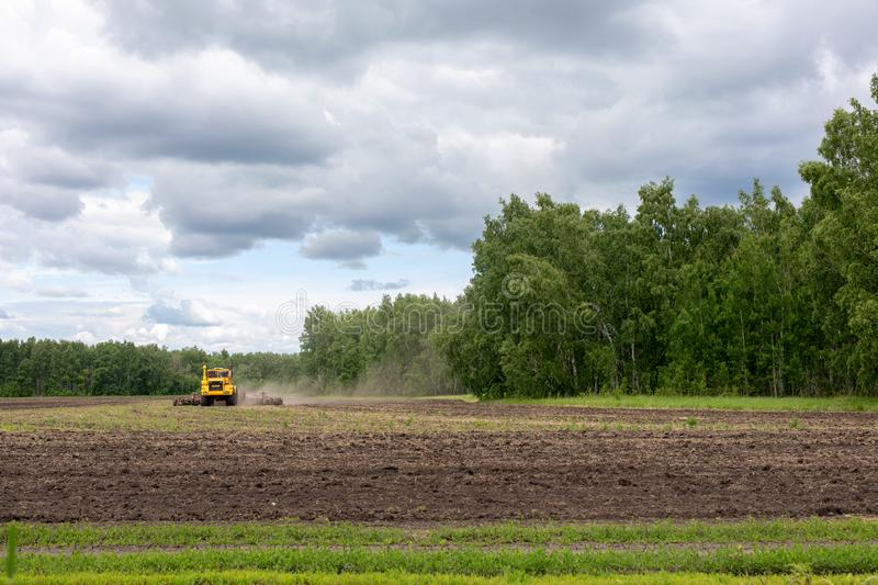 Ploughing Tractor At Field Cultivation Work. machine plows the field, harrows and cultivates the soil for sowing grain royalty free stock photo