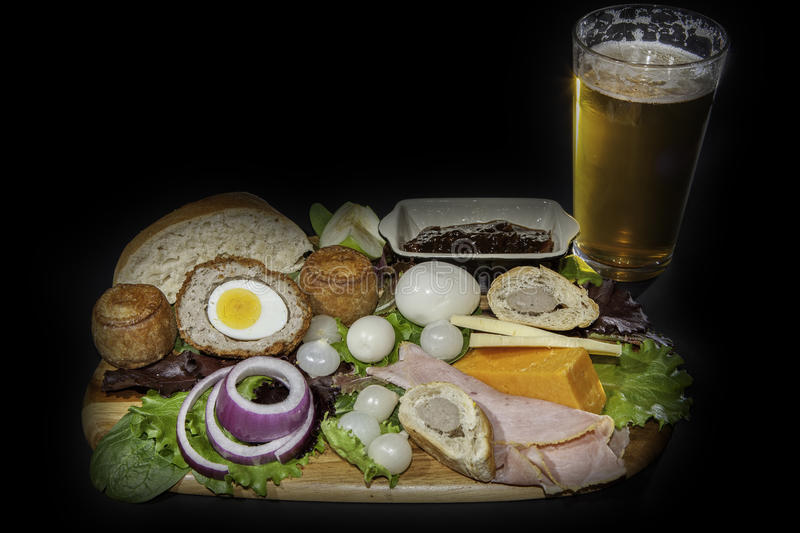 Ploughman`s Pub Lunch. Ploughman's pub lunch including scotch egg; pork pies, ham; pickled onions and cheese served with a pint of lager beer. Isolated royalty free stock photography