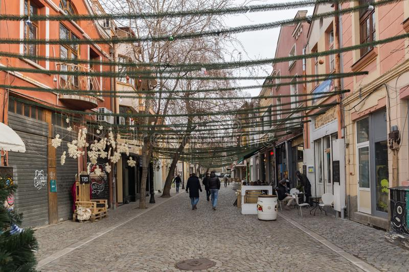 Walking people and Street in district Kapana, city of Plovdiv, Bulgaria. PLOVDIV, BULGARIA - DECEMBER 30, 2016: Walking people and Street in district Kapana royalty free stock images