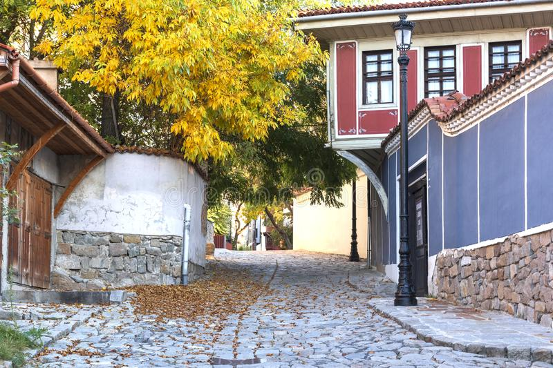 Plovdiv, Bulgaria.The street of the Old Town with renaissance buildings is decorated with autumn tree and fallen leaves royalty free stock image