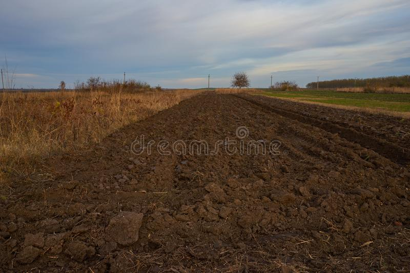 Plowed field in autum at dusk. Partial plowed field in autum at dusk with a beautiful sky in a rural zone stock images