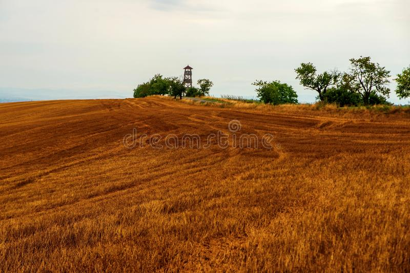 Plowed field with lookout tower and trees stock images