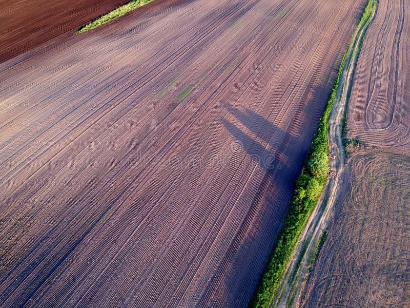 Plowed odlade det åkerbruka fältet för vårtid som var flyg- arkivfoton