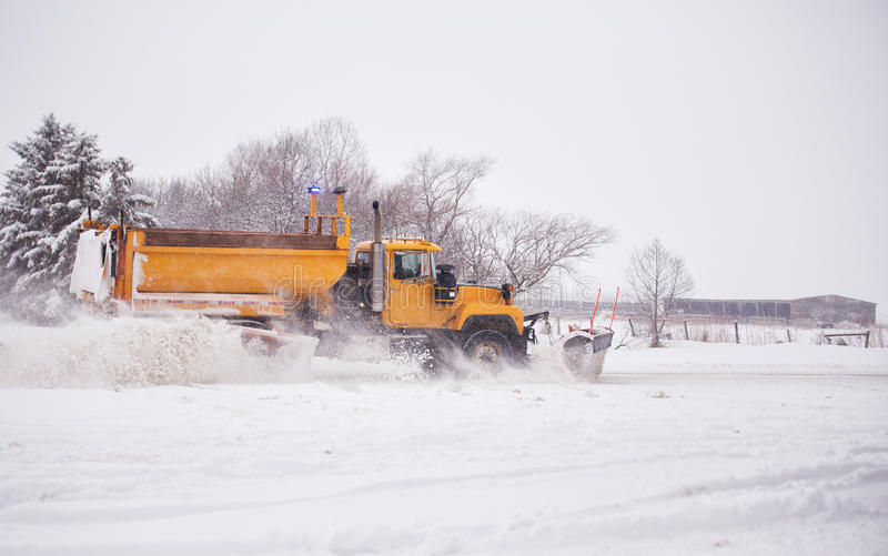 Plowing snow. Heavy industrial dump truck with attached plow speeding down a highway clearing snow off the road in rural landscape stock photo