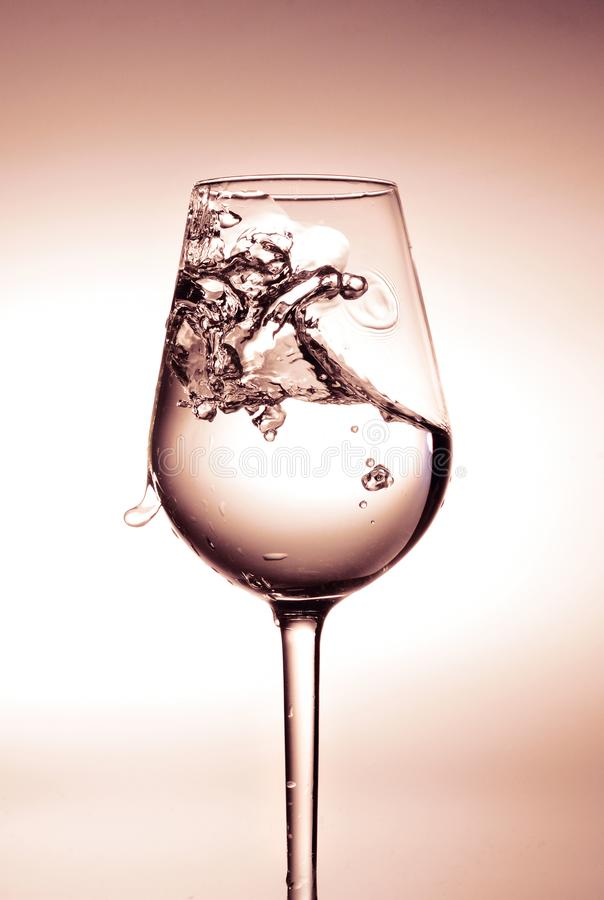 Pluśnięcie woda w szkle i kropli Światła białe w centrum i jasnobrązowy wokoło krawędzi zdjęcie stock