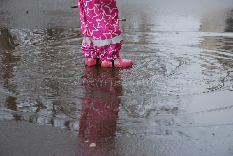Pluśnięcia i okręgi na kałuży od dziecka ` s cieków Nogi dziewczyna troszkę biegają wokoło w kałuży zdjęcie royalty free