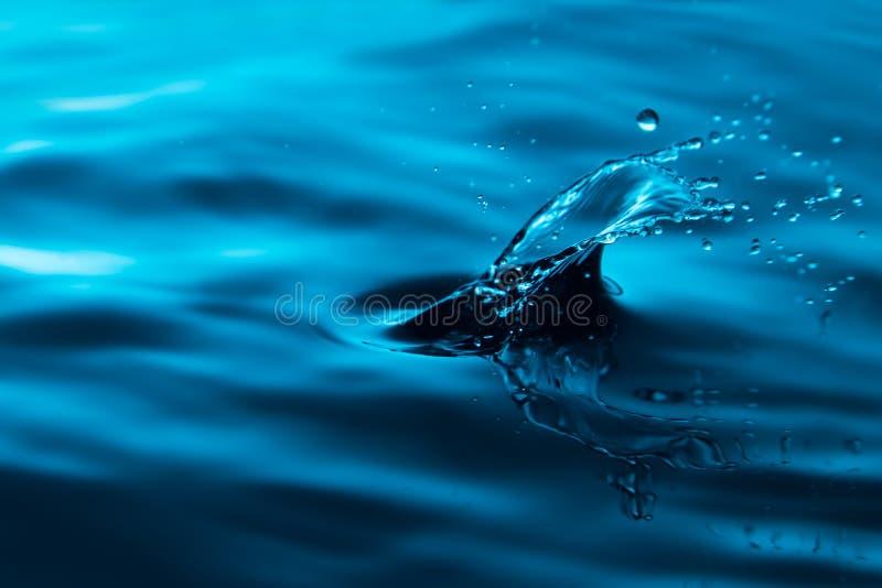 Pluśnięcie błękitne wody up i mały fala zakończenie zdjęcie stock