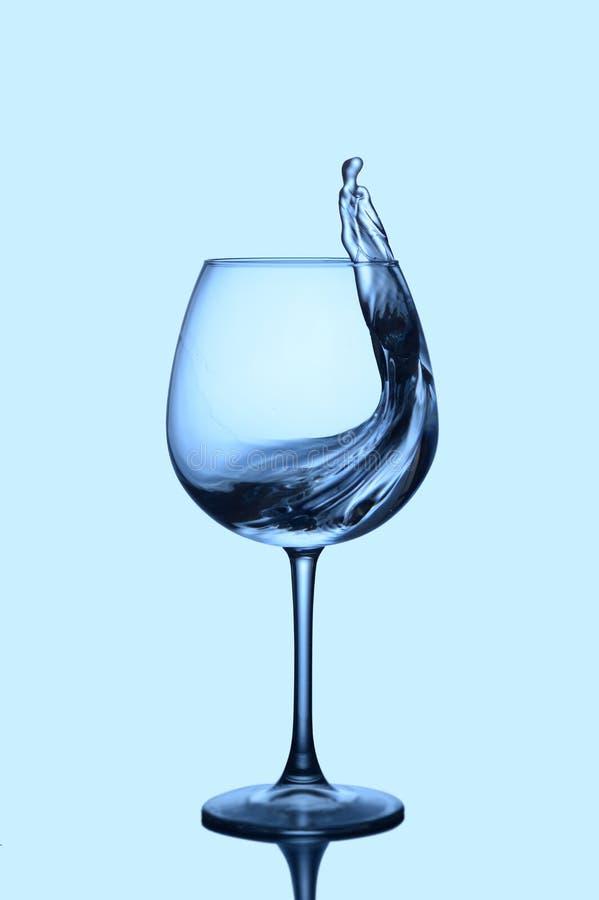 Pluśnięcie błękitne wody w szkle na zmroku - błękit obraz royalty free