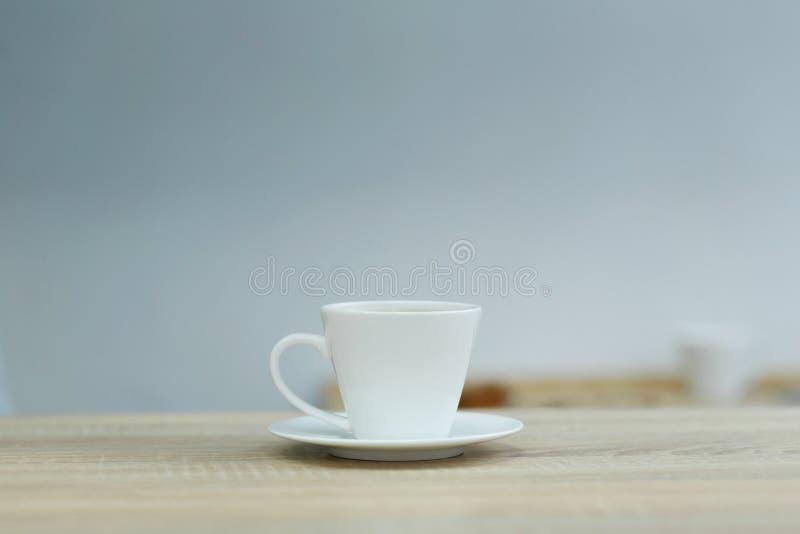 Pluśnięcie w białym filiżanka kawy na drewnianym stole zdjęcia stock