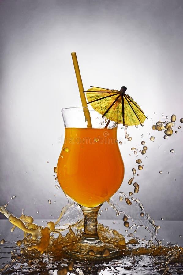 Pluśnięcie w szkle pomarańczowy alkoholiczny tropikalny koktajlu napój z parasolem i słomą obraz stock
