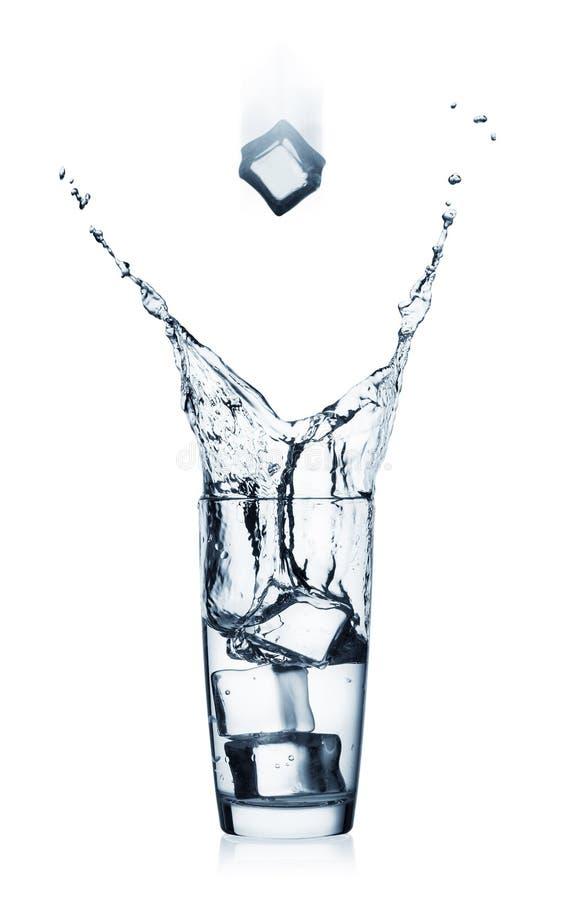 Pluśnięcie w szkle z jasną wody i latania kostką lodu zdjęcia royalty free