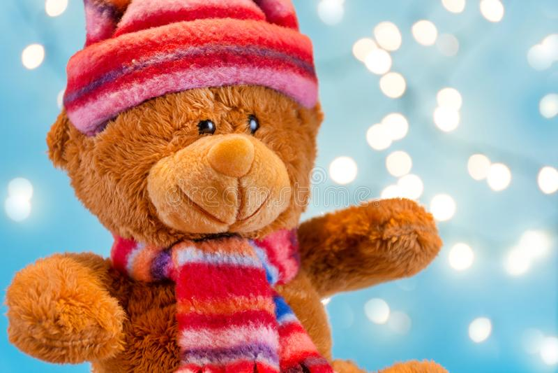 Plucheachtig draag stuk speelgoed met de wintersjaal en hoeden en Kerstmislichten op blauwe vage achtergrond stock foto