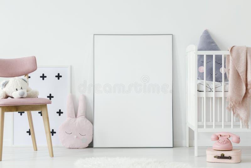 Pluchestuk speelgoed op roze houten stoel naast lege affiche met model royalty-vrije stock foto's