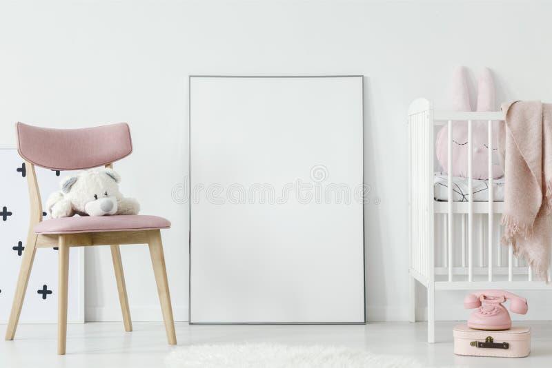 Pluchestuk speelgoed op roze stoel naast affiche met model in baby` s roo royalty-vrije stock foto