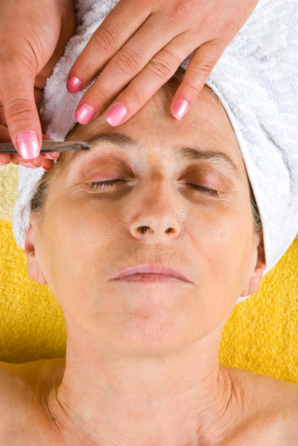 Plucking eyebrows to senior woman royalty free stock image