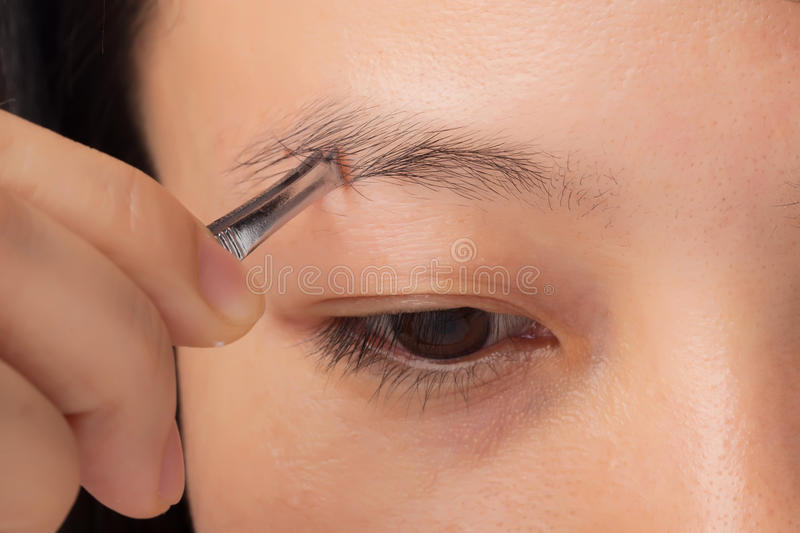 Plucking eyebrows stock photography