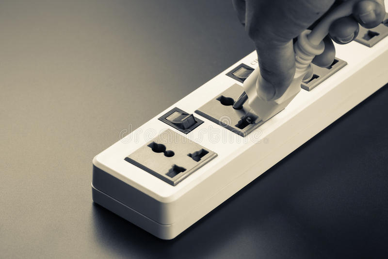 Plug in. Closeup hand insert plug into multiple socket bar stock photography