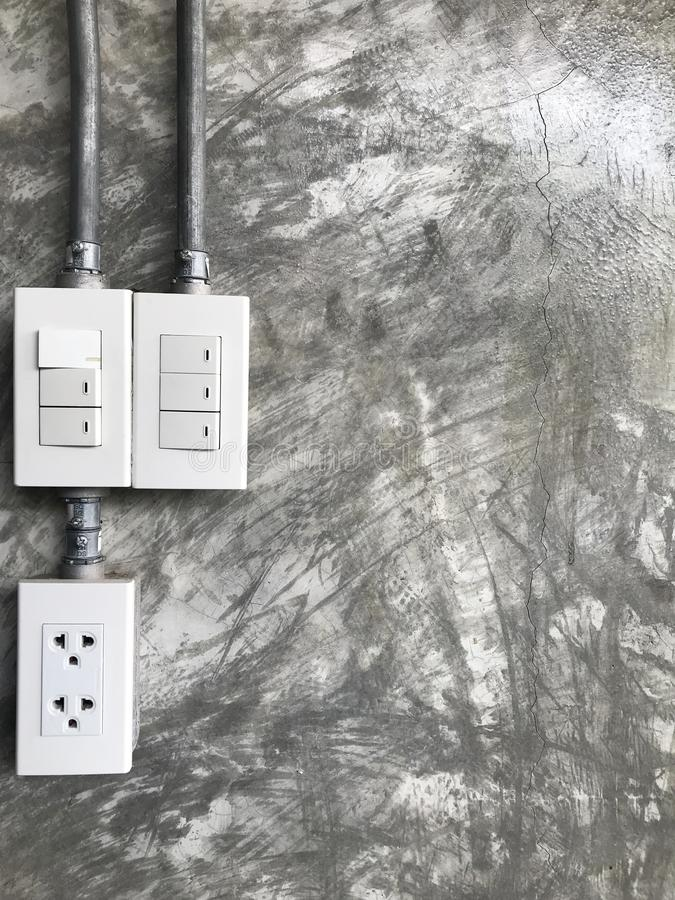 Plug the power outlet and the power switch on the cement wall stock photos
