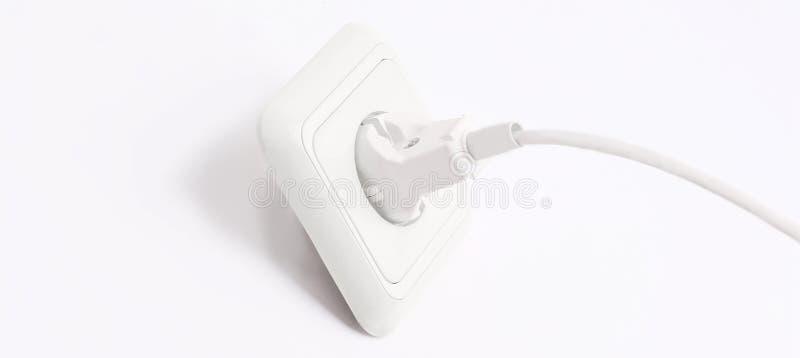 Plugga in i ett elektriskt uttag bakgrund isolerad white arkivbild