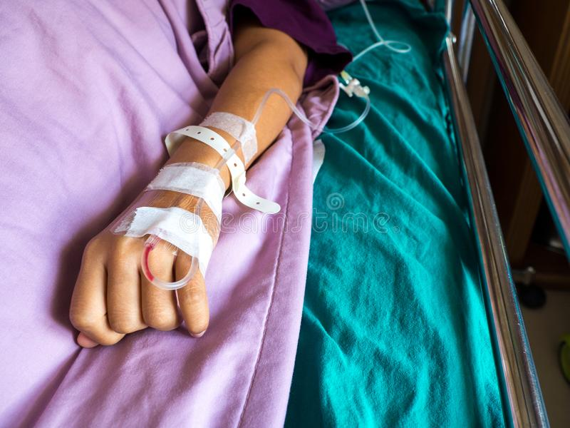 Pluggar den övre handen för slutet av den asiatiska kvinnapatienten med droppandehälerit för injektion in handen droppdroppande m royaltyfria foton