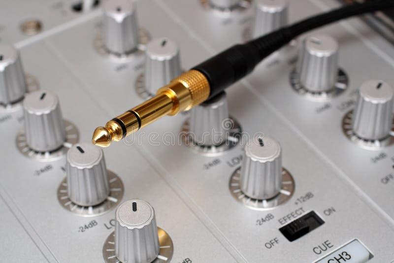 Plugue do ouro no misturador da música do DJ foto de stock