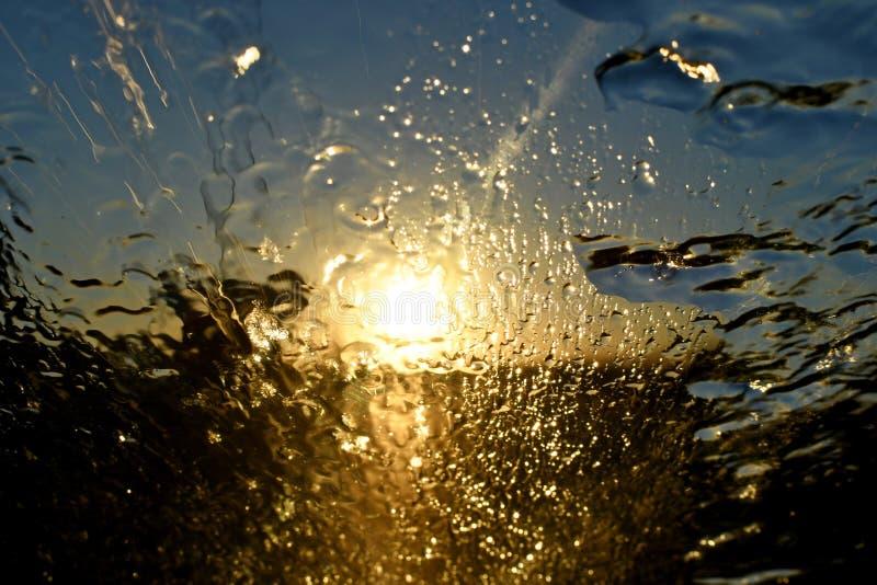 Pluie d'abrégé sur coucher du soleil d'or sur le pare-brise avant de voiture image stock