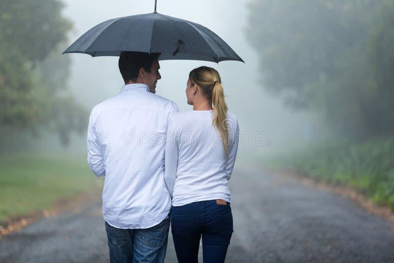 Pluie de marche de couples images stock