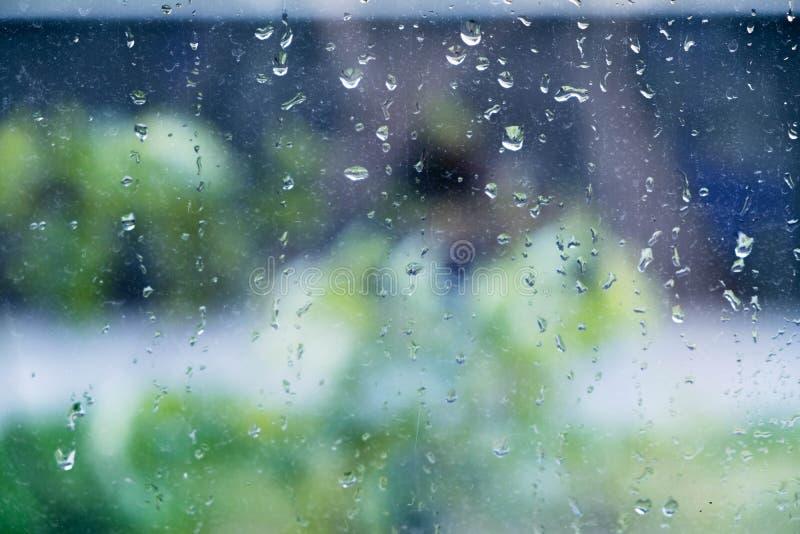 Pluie sur une fenêtre La pluie sur une fenêtre brouille l'extérieur à l'hors du modèle de foyer Baisses sur le verre Pluie sur la images libres de droits