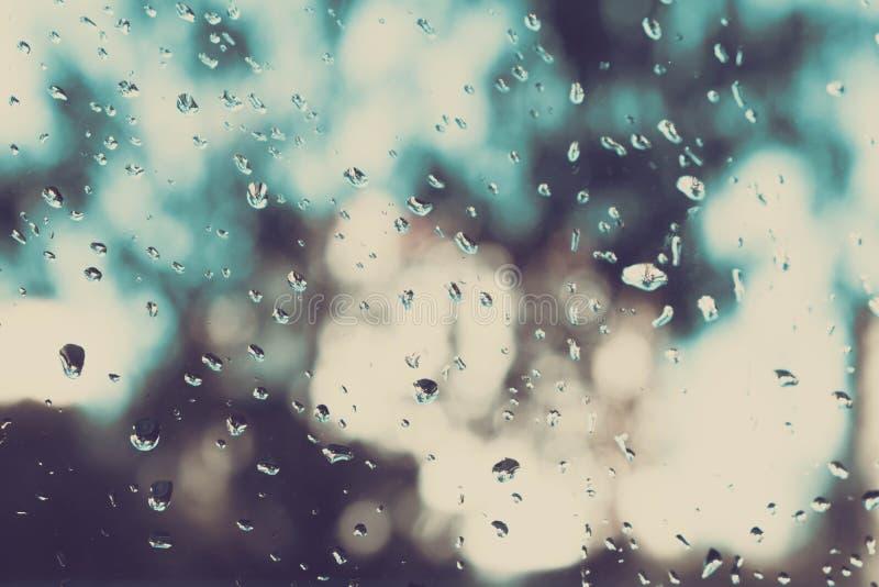 Pluie sur une fenêtre La pluie sur une fenêtre brouille l'extérieur à l'hors du modèle de foyer Baisses sur le verre Pluie sur la photos stock