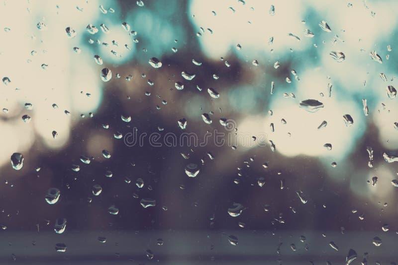 Pluie sur une fenêtre La pluie sur une fenêtre brouille l'extérieur à l'hors du modèle de foyer Baisses sur le verre Pluie sur la images stock