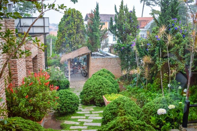 Pluie tropicale dans la cour avec les buissons verts et une moto sous un auvent image stock