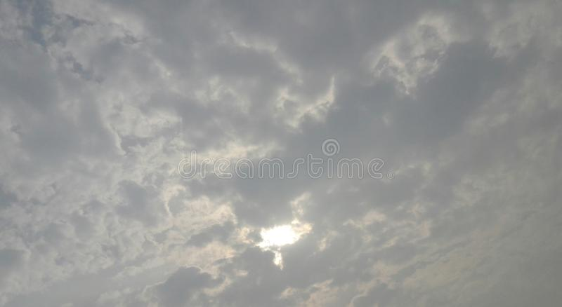 pluizige wolken in hemel die zon behandelen royalty-vrije stock foto