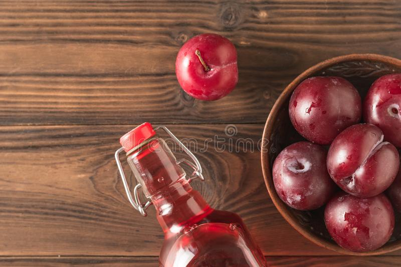 Plum alcoholic drink and plum berries on the table. Flat lay. royalty free stock photography