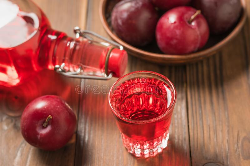 Plum alcoholic drink and plum berries on the table. Flat lay. Plum alcoholic drink and plum berries on the table. Homemade alcoholic drink made from berries royalty free stock photo